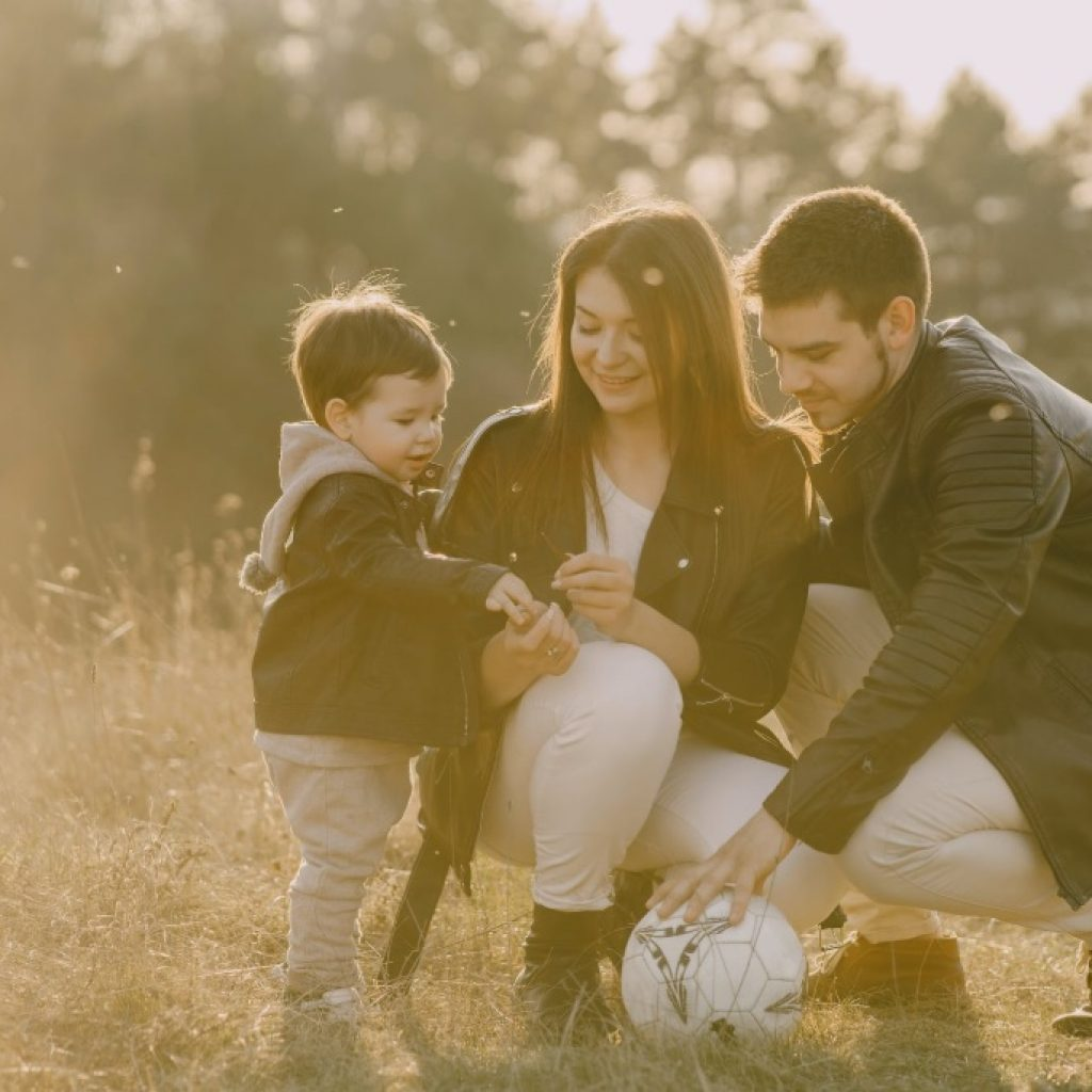 Husband and wife with son outside playing soccer.
